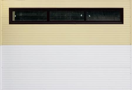 textura: piastrelle a parete con una lunga finestra orizzontale ea cuciture orizzontali, dipinte nei colori bianco e beige Archivio Fotografico