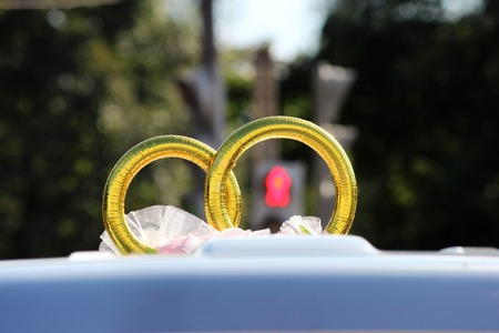 marry go round: wedding rings as decoration on a machine with a traffic signal on the crosswalk in the background Stock Photo
