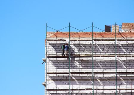 los trabajadores en el andamio están construyendo la casa de nueve pisos de bloques y ladrillos.