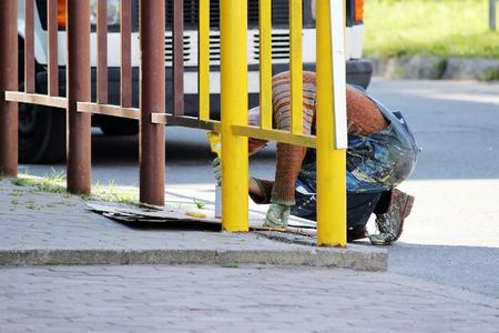 colourer: The house painter paints a fence yellow oil paint Stock Photo