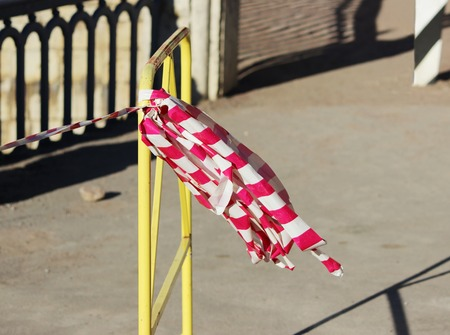 attached: red white warning tape fencing is attached on a yellow fence