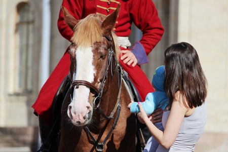 vestidos de epoca: woman and child stroking a red horse on which the rider sits, dressed in period costume.