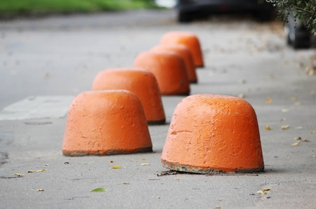 sidewalk near the house and orange hemisphere parking strengthened against the entry of vehicles. Relevant when the danger of terrorist attacks. Stock Photo