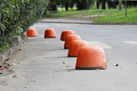 relevant: sidewalk near the house and orange hemisphere parking strengthened against the entry of vehicles. Relevant when the danger of terrorist attacks. Stock Photo