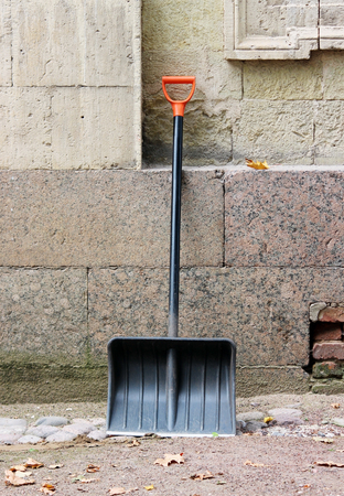 seasonal worker: New black shovel with orange handle is leaning against the wall of the palace waiting for clearance from the alley of fallen leaves.