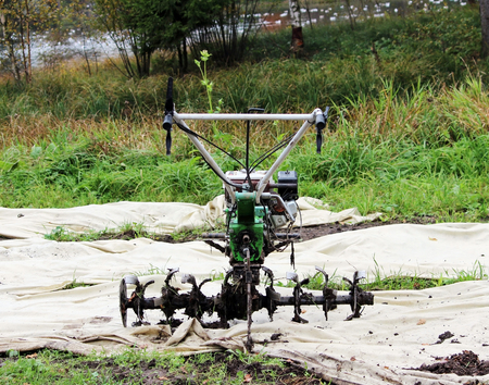 motor hoe: working motor-cultivator tiller in Gatchina park is on the ground waiting for work Stock Photo