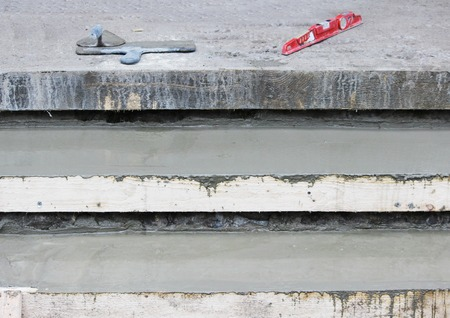 Tools: Two trowel, level on the steps and wooden formwork filled with concrete mix Stock Photo