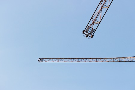 is cloudless: two jib cranes against a cloudless blue sky