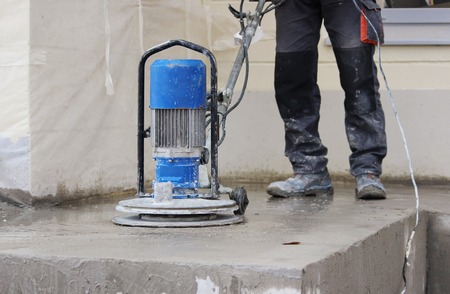 male worker works with the diamond grinding machine, polishing the porch in front of the office building.Grinding the cement floor machine and construction worker Banque d'images