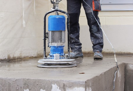 floor machine: male worker works with the diamond grinding machine, polishing the porch in front of the office building.Grinding the cement floor machine and construction worker Stock Photo