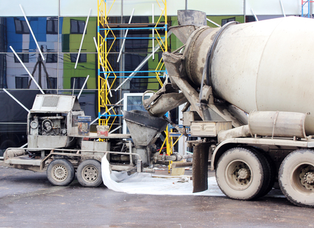 scaffolds: concrete pump and concrete mixer to work together to pouring cement floors in the shopping center for repair Stock Photo