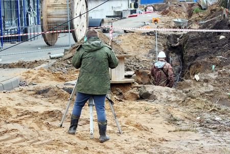 geodesist: Two surveyor builder at a construction site near the apartment building