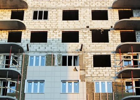 windows in a newly built house. wall structure with insulated non-combustible material basalt fiber tiled. telescopic rack formwork monolithic slabs in the construction of a multistory building
