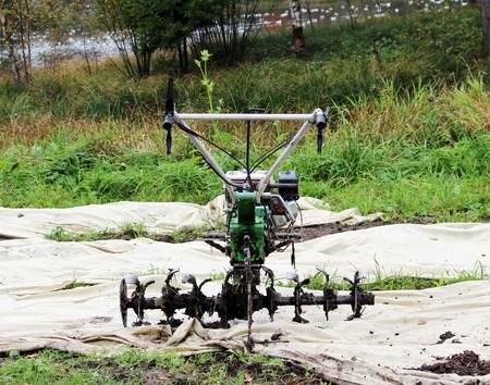 working motor-cultivator tiller in Gatchina park is on the ground waiting for work Stock Photo