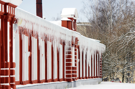 icicles on building roof at sunny winter day. Stock Photo