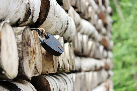 texture of birch logs stacked pattern on the walls of the house and lock the metal shutters on the windows.