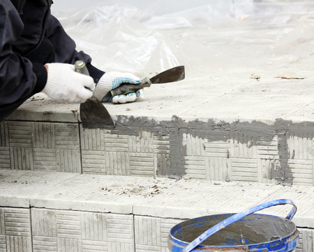 glosses: tiler glosses over gaps between the stacked stone tiles on the steps in the repair of the office building.