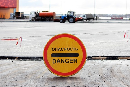 danger warning sign that prohibits the passage to the parking lot, which is repaired. inscription in Russian says: danger . Stock Photo