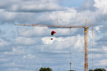 dangerous paramotor flying around the crane on the construction site.