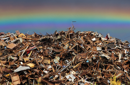 pile of scrap black metal piled in the open air and rainbow.