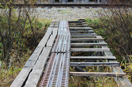 destroyed a bridge across the ditch from wooden planks and metal profiles Stock Photo