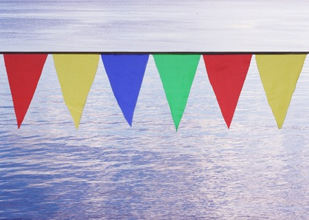 whiff: Multi Colored Triangular Flags Hanging in the Sky at an Outdoor on the background of blue water