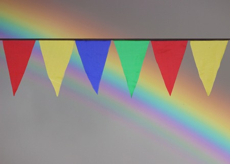 whiff: Multi Colored Triangular Flags Hanging in the Sky at an Outdoor against the backdrop of a rainbow