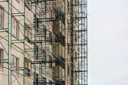 scaffolds: green construction metal timber in beige house under construction at the time of finishing and plastering work