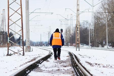 オレンジ色で鉄道員の制服のトラックの上を歩く