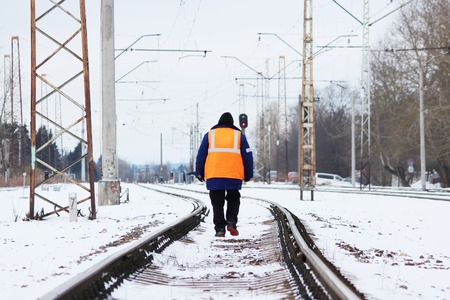 railroad worker in orange uniforms walking on the tracks