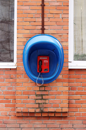 pay wall: Red phone public apparatus protected blue booth on the brick wall of the house