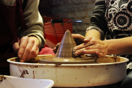 potters wheel: experienced master potter teaches the art of making pots of clay on the potters wheel.