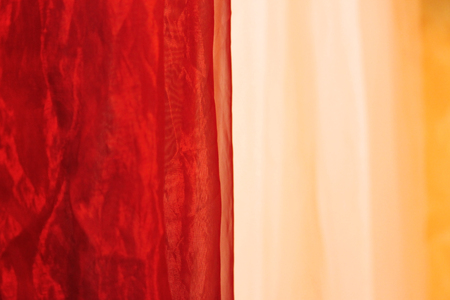 soft textile: Soft coral and beige chiffon, fabric texture, textile background. red and beige tulle hanging at the entrance to a massage parlor