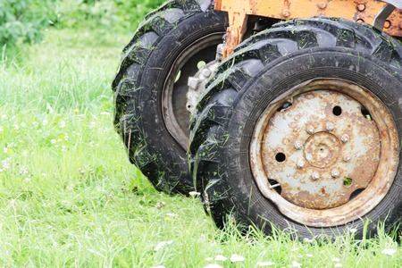 Old work tractor wheel who mows the grass on the field in summer.