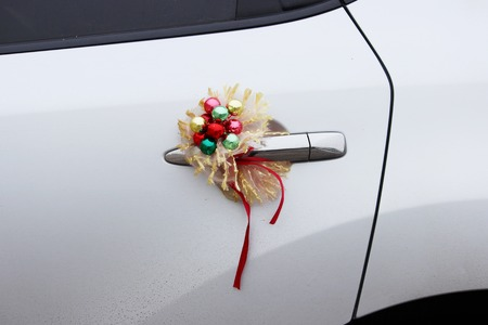 New Year wedding decoration on the door of a white car