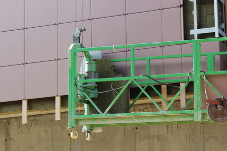 work with green front two suspended cradle without workers on a newly built high-rise building
