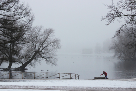 mystique: Woman catches a coin into the well in the Jordanian Gatchina Park in the fog in winter.