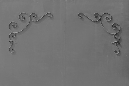 uniform curls: black and white photo metal grey gates with a pattern in the form of curls covered with paint