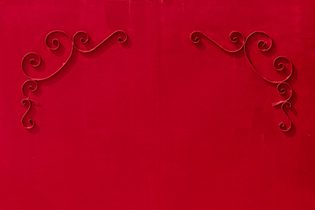 uniform curls: metal red gates with a pattern in the form of curls covered with paint Stock Photo
