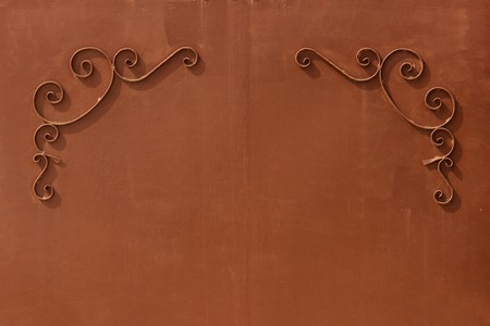 uniform curls: metal brown gates with a pattern in the form of curls covered with paint