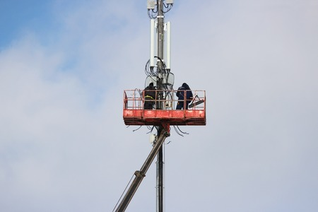 Two workers assemble equipment for telecommunications on the tower with the help of the lift in the winter.