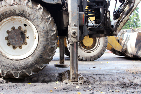 hardening: Tractor strong outrigger stabilizing legs extended to stabilize and steady state when digging the soil under the road repair
