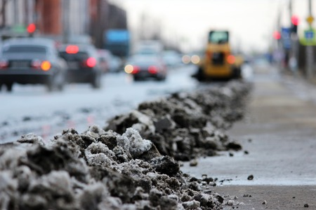 tractor cleans the road in the city of dirty snow.