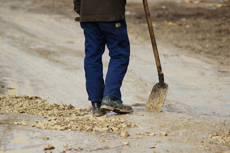 A worker with a shovel strews gravel in pits to level the road. Stock Photo