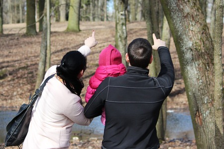 Family for a walk. Dad and mom show daughter on squirrel, which sits on tree Stock Photo