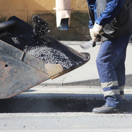 Road worker in overalls is poured with hot tar on the edge of the road strip when repairing the road