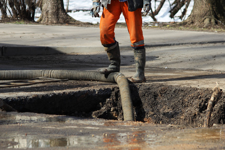 eliminating: Pumping water out of the pit when eliminating an accident: rupturing pipes with cold water. Stock Photo