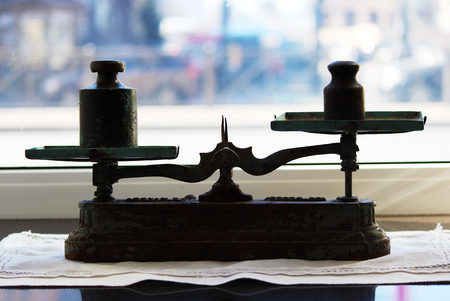 Old scales with cups stand on the windowsill near the window.