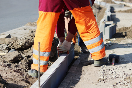 Repair of the sidewalk. Professional working masons in overalls lay curbs before laying stone paving slabs.
