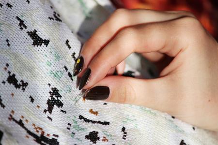 Meisje borduursteken borduurt op een witte doek foto